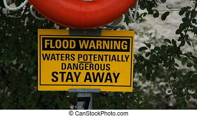 Flood warning sign with river.