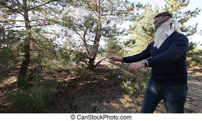 Playing hide and seek - In coniferous forest blindfolded guy...
