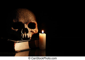 Skull On Book - One human skull on old book near lighting...