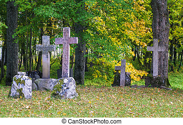 Old stone crosses on graves with autumn trees around