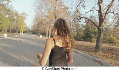 Slim girl jogging through beautiful autumn park view from...