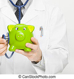 Doctor holding stethoscope and piggybank