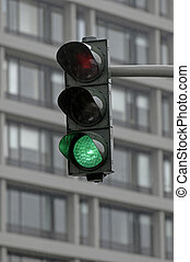 green traffic light in front of a modern building