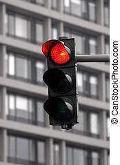 red traffic light in front of a modern building