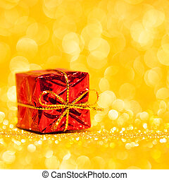 Red decorative box with holiday gift on gold glitters...
