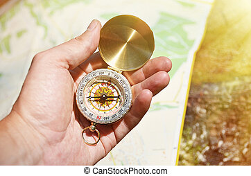 Vintage compass in the hand against a map