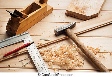 carpenter tools, plane, hammer,meter, nails,shavings, and chisel over wood table