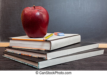 School time - Apple on books and chalkboard for background