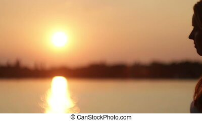 girl sitting by the lake at sunset - girl sitting by the...