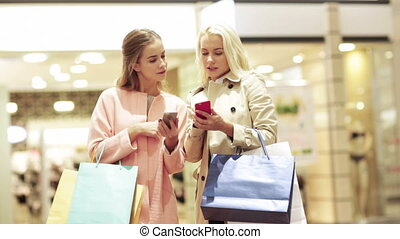 happy women with smartphones and shopping bags