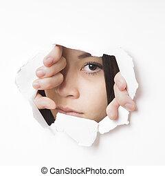 young asian woman peeking - young asian woman tearing hole...