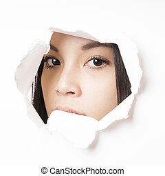 young asian woman peeking through hole torn in paper wall