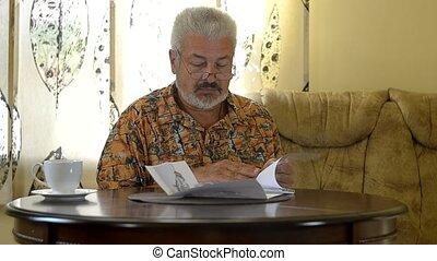 Senior man sitting at table working