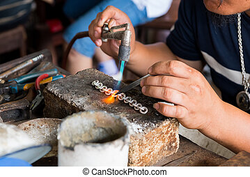 jeweler's hands while working making jewelry in Vientiane,...