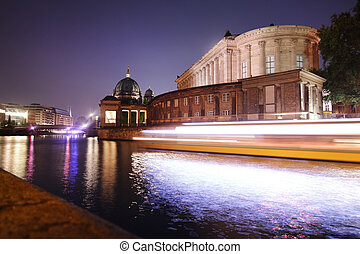 Lights of a passing boat on the spree river below the museum isle in Berlin
