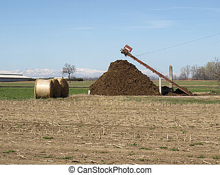 Manure - Heap of manure and straw bales in a field
