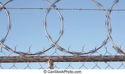 Woman Climing Razor Wire Fence - Woman with a ponytail...