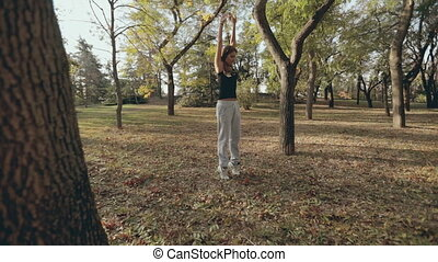 Girl in sportswear doing workout in the fresh air -...