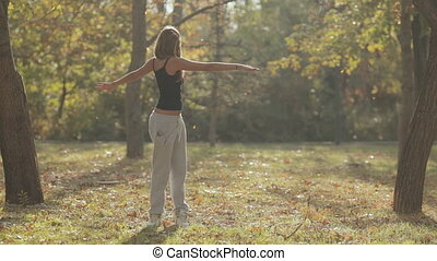 Young girl doing a workout in the forest under the falling...