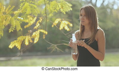 Beautiful girl in the park opens and drinks pure water from...