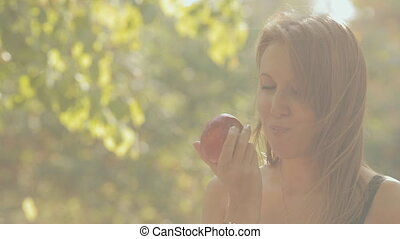 The girl eats a red apple in the forest