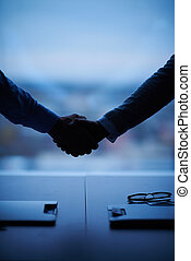 Companionship - Outline of handshake of two businessmen over...