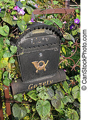 Cloes up of a mailbox on the overgrown fence