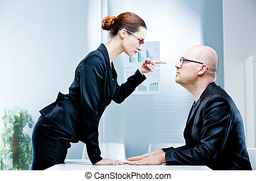woman reproaching man at work - business woman pointing out...