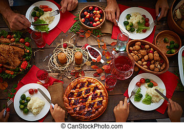 Thanksgiving dinner - Hands of people over plates with...