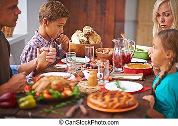 Giving thanks for dinner - Portrait of modern family praying...