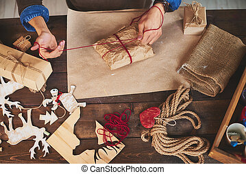 Wrapping presents - Male hands wrapping xmas gifts into...