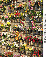 gravestones and tombs in the cemetery with many flowers