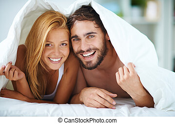Sweethearts - Affectionate man and woman under blanket...