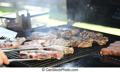 Barbeque Grilling Lamb Chops - A man grills lamb chops on...