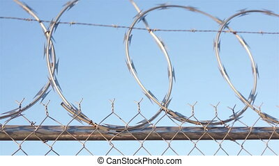 Razor Wire Fence Shaking Pan - Panning shot of a razor wire...