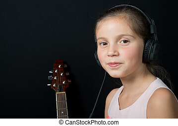 a cute little girl listening to music with headphones - a...