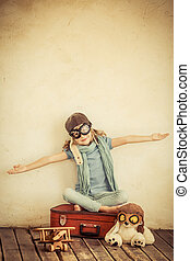 Pilot - Happy child playing with toy airplane at home Retro...