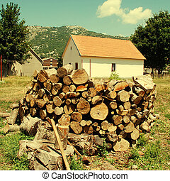 Country house with pile of firewood and mountains on...