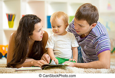 Young happy family with baby son reading children book -...