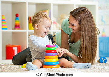 cute mother and child boy play together indoor at home -...