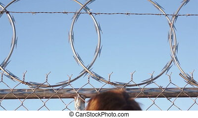 Man Climbing Razor Wire Fence - Man climbs onto a razor wire...