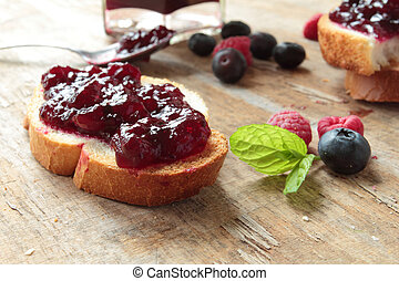 Crunchy bread with sweet jam on a wooden table