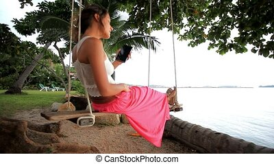 Woman on a swing at palm tree and talking by phone. Koh...