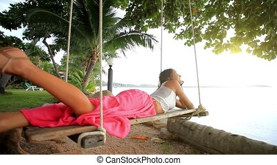 Woman lies on a swing at palm tree and talking by phone. Koh...