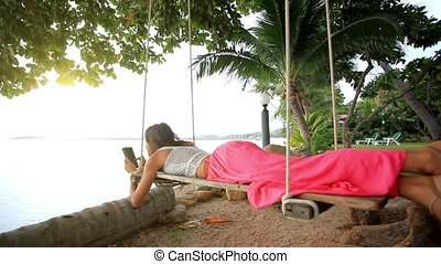 Woman lies on a swing at palm tree uses smartphone and takes...