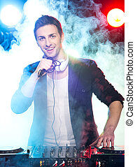 DJ - Portrait of a young dj with mixer, on foggy background