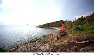Young woman standing on a rockis taking photo Koh Samui...