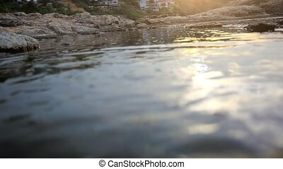 Beautiful rocky landscape sunset in the sea with stones on...