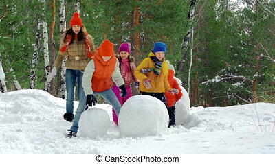 Winter Creativity - Group of kids making a snowman together