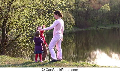 mother with children on spring pond